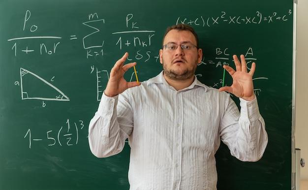 Onder de indruk van jonge leraar met een bril die voor het bord in de klas staat en naar de voorkant kijkt met telstokken
