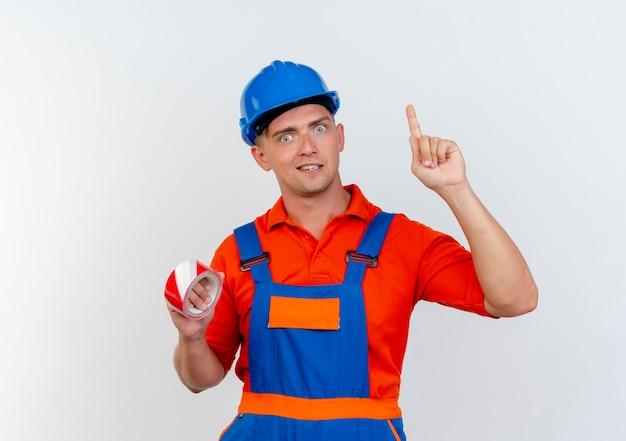 Onder de indruk van jonge mannelijke bouwer die uniform draagt en een veiligheidshelm draagt die ducttape vasthoudt en naar boven wijst