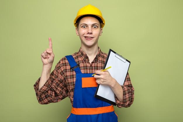 Onder de indruk van jonge mannelijke bouwer met klembord in uniform