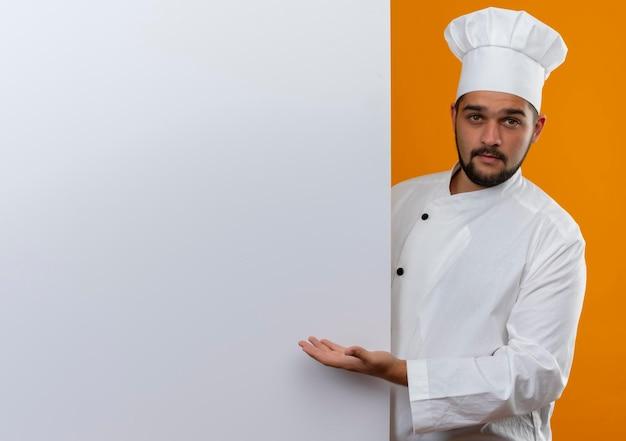 Onder de indruk van jonge mannelijke kok in chef-kok uniform die achter staat en met de hand wijst naar een witte muur die er geïsoleerd uitziet op een oranje muur met kopieerruimte