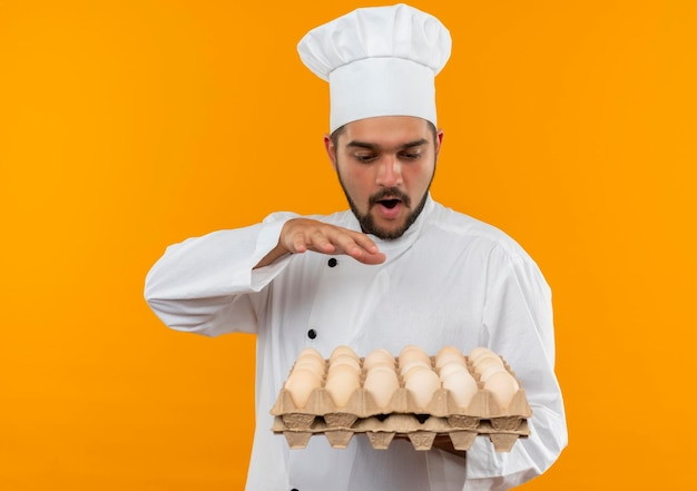 Onder de indruk van jonge mannelijke kok in uniform van de chef-kok die een doos eieren vasthoudt en bekijkt en de hand op de lucht houdt, geïsoleerd op een oranje muur