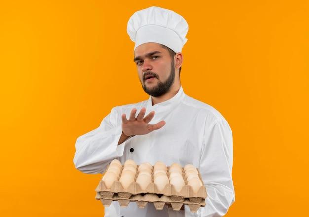 Onder de indruk van jonge mannelijke kok in uniform van de chef-kok die een doos eieren vasthoudt en de hand boven hen houdt, geïsoleerd op een oranje muur