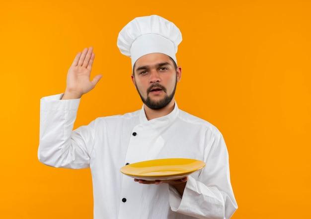 Onder de indruk van jonge mannelijke kok in uniform van de chef-kok die een leeg bord vasthoudt en de hand opsteekt geïsoleerd op een oranje muur met kopieerruimte