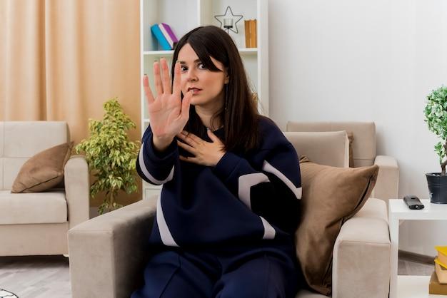 Onder de indruk van jonge mooie blanke vrouw zittend op een fauteuil in ontworpen woonkamer hand op de borst zetten en stop gebaar doen