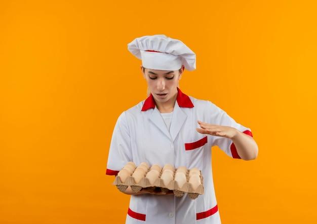 Onder de indruk van jonge mooie kok in uniform van de chef-kok die een doos eieren vasthoudt en kijkt terwijl hij de hand op de lucht houdt geïsoleerd op een oranje muur met kopieerruimte