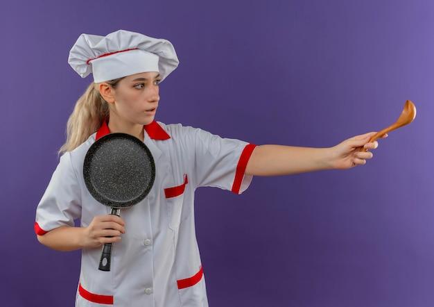 Onder de indruk van jonge, mooie kok in uniform van de chef-kok die een koekenpan vasthoudt en naar de zijkant kijkt en een lepel uitrekt die op een paarse muur is geïsoleerd