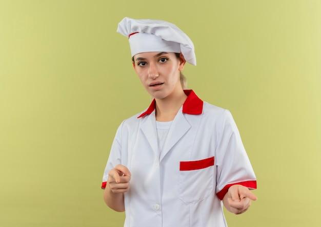 Onder de indruk van jonge mooie kok in uniform van de chef-kok die je gebaar doet geïsoleerd op groene muur met kopieerruimte copy