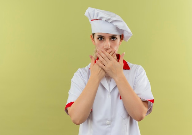 Onder de indruk van jonge mooie kok in uniform van de chef-kok die mond sluit met handen geïsoleerd op groene muur met kopieerruimte