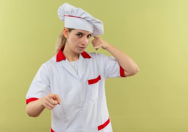 Onder de indruk van jonge mooie kok in uniform van de chef-kok die oproepgebaar doet en geïsoleerd op groene muur wijst met kopieerruimte
