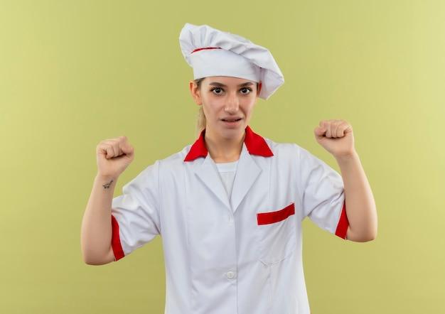 Onder de indruk van jonge mooie kok in uniform van de chef-kok die vuisten opheft die op groene muur worden geïsoleerd