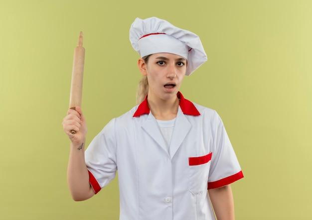 Onder de indruk van jonge mooie kok in uniform van de chef-kok met deegroller geïsoleerd op groene muur