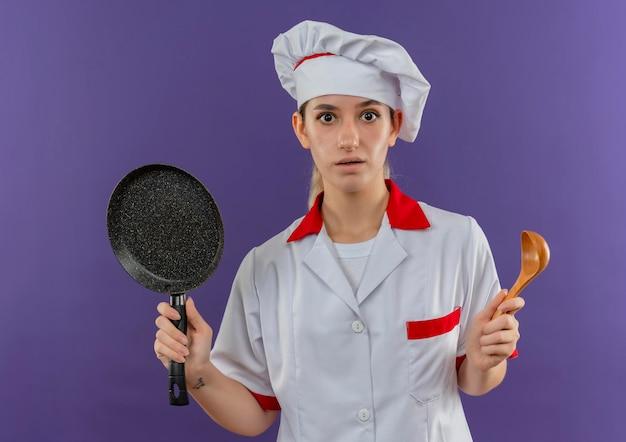 Onder de indruk van jonge mooie kok in uniform van de chef-kok met koekenpan en lepel geïsoleerd op paarse muur