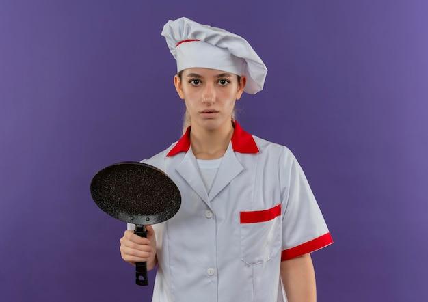 Onder de indruk van jonge mooie kok in uniform van de chef-kok met koekenpan op zoek geïsoleerd op paarse muur