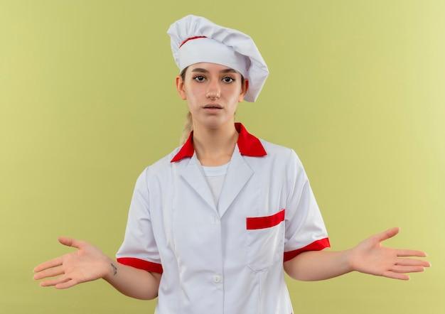 Onder de indruk van jonge mooie kok in uniform van de chef-kok met lege handen geïsoleerd op groene muur