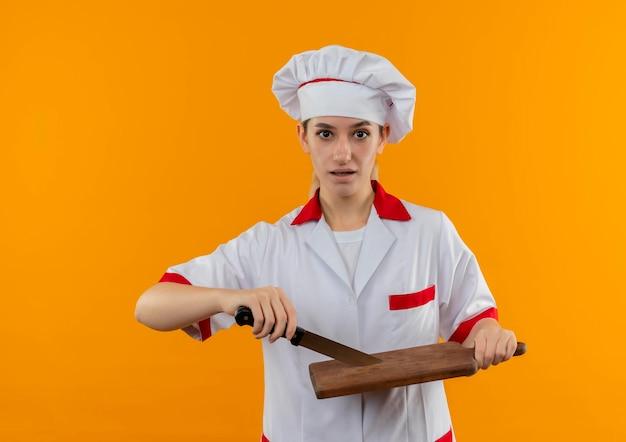 Onder de indruk van jonge mooie kok in uniform van de chef-kok met mes en snijplank geïsoleerd op oranje muur