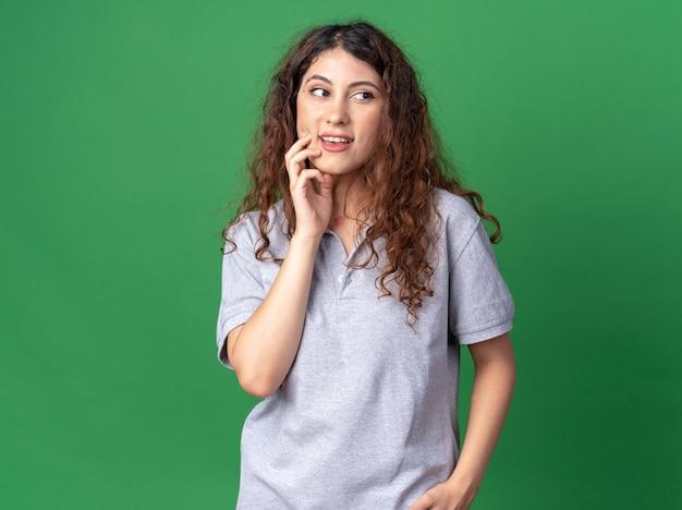 Onder de indruk van jonge mooie vrouw die de kin aanraakt en naar de kant kijkt die op een groene muur is geïsoleerd met kopieerruimte