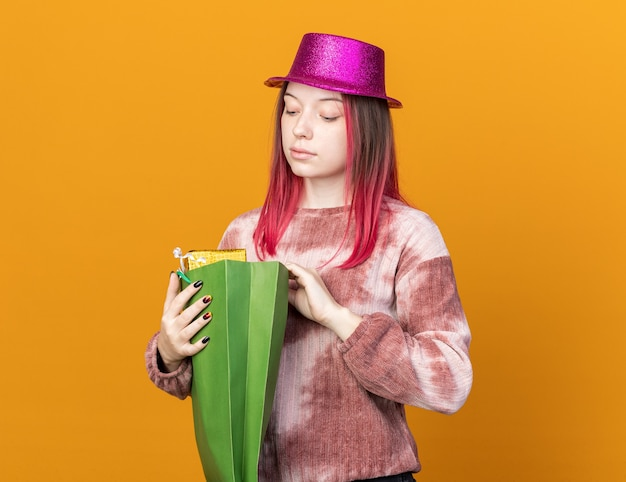 Onder de indruk van jonge mooie vrouw die een feesthoed draagt en naar een cadeauzakje kijkt dat op een oranje muur is geïsoleerd
