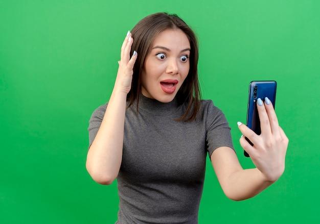 Onder de indruk van jonge mooie vrouw die en mobiele telefoon bekijkt en hoofd aanraakt