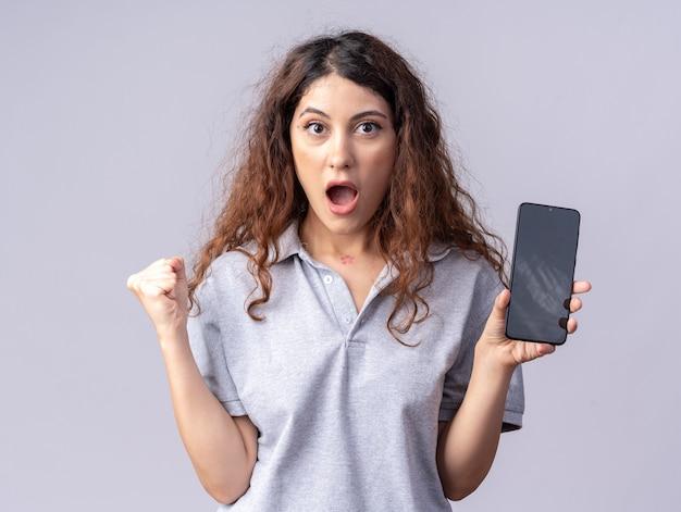 Onder de indruk van jonge mooie vrouw die naar voren kijkt en mobiele telefoon naar voren laat zien die ja gebaar doet geïsoleerd op een witte muur
