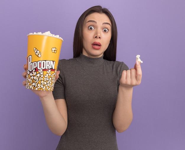 Onder de indruk van jonge mooie vrouw met emmer popcorn en popcorn stuk geïsoleerd op paarse muur