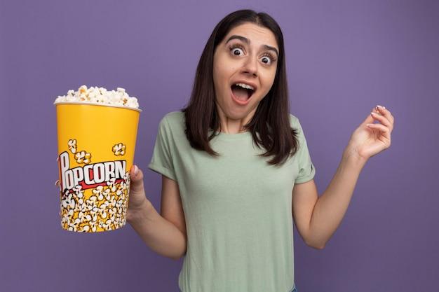 Onder de indruk van jonge mooie vrouw met emmer popcorn en popcorn stuk kijkend naar de voorkant geïsoleerd op paarse muur