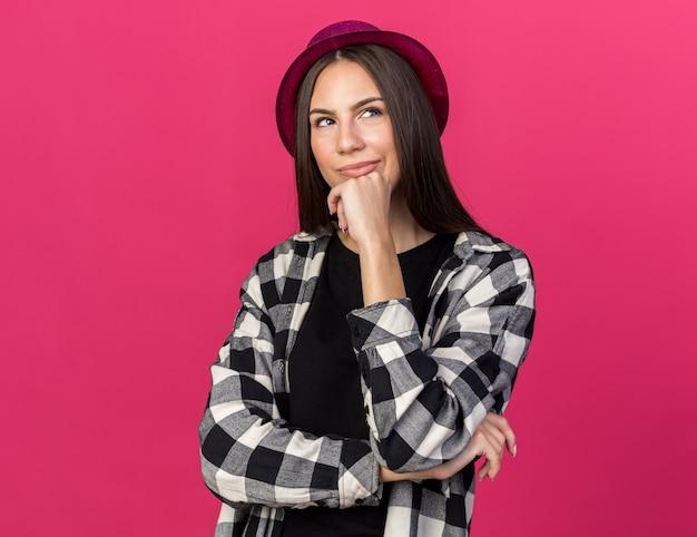 Onder de indruk van jonge mooie vrouw met feesthoed die hand op de kin legt die op roze muur wordt geïsoleerd