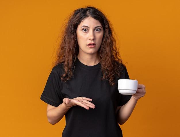 Onder de indruk van jonge mooie vrouw met kopje thee met lege hand kijkend naar voorkant geïsoleerd op oranje muur