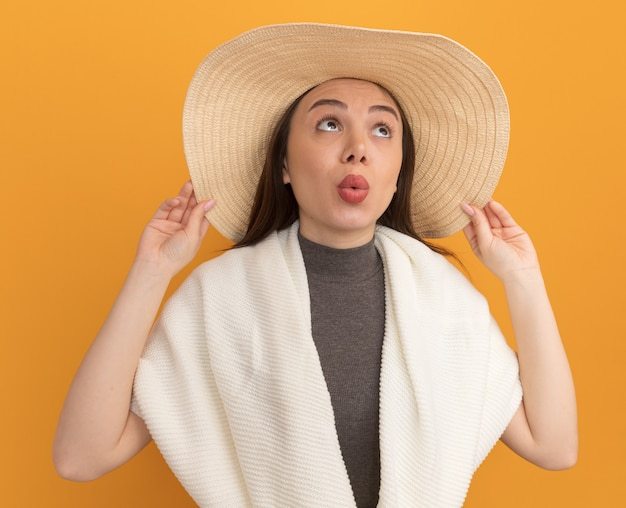 Onder de indruk van jonge mooie vrouw met strandhoed die hoed grijpt en omhoog kijkt met getuite lippen