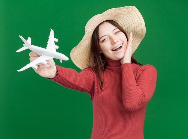 Onder de indruk van jonge mooie vrouw met strandhoed die modelvliegtuig naar voren strekt en naar de camera kijkt die hand op het gezicht zet dat op groene muur wordt geïsoleerd