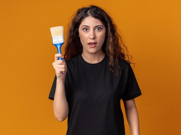 Onder de indruk van jonge mooie vrouw met verfborstel kijkend naar de voorkant geïsoleerd op een oranje muur met kopieerruimte