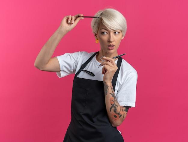 Onder de indruk van jonge mooie vrouwelijke kapper in uniform bedrijf schaar met kam geïsoleerd op roze muur