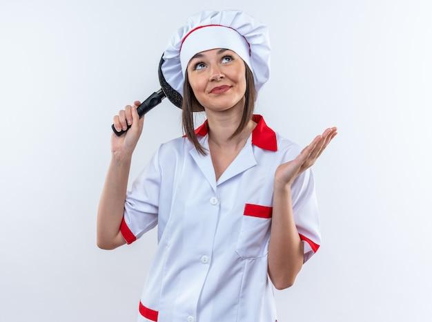Onder de indruk van jonge vrouwelijke kok in uniform van de chef-kok met koekenpan achter hoofd geïsoleerd op een witte achtergrond