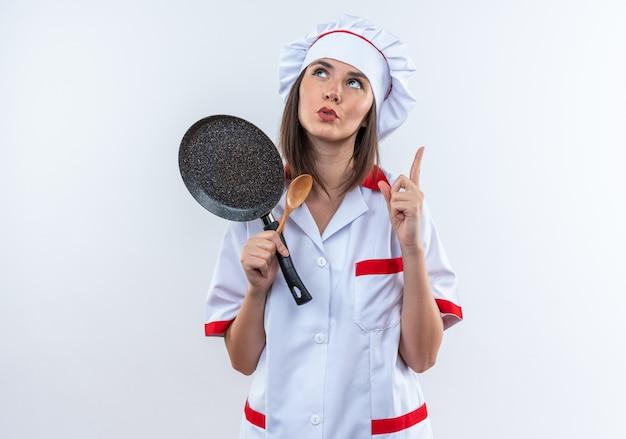Onder de indruk van jonge vrouwelijke kok in uniform van de chef-kok met koekenpan met lepel wijst naar boven geïsoleerd op een witte muur