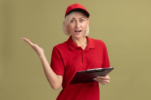 Onder de indruk van middelbare leeftijd blonde bezorger in rood uniform en pet met klembord met lege hand