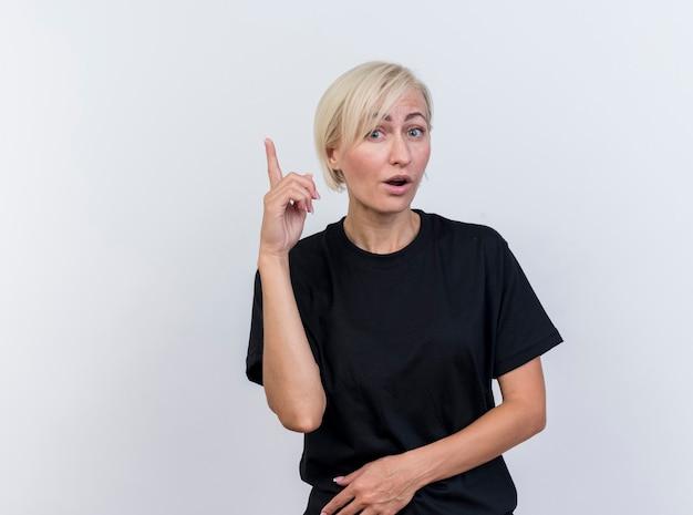 Onder de indruk van middelbare leeftijd blonde slavische vrouw die camera bekijkt die omhoog wijst geïsoleerd op witte achtergrond met exemplaarruimte