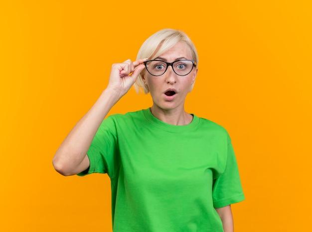Onder de indruk van middelbare leeftijd blonde slavische vrouw die een bril draagt die hen grijpt die naar voorzijde kijkt die op gele muur met exemplaarruimte wordt geïsoleerd