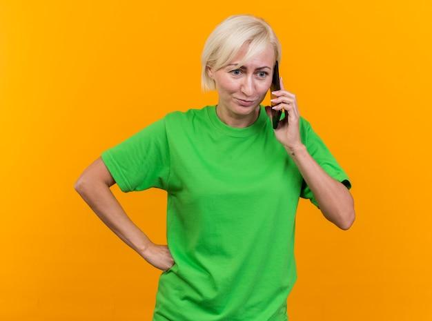 Onder de indruk van middelbare leeftijd blonde slavische vrouw die hand op taille houdt die rechtop kijkt pratend aan telefoon die op gele achtergrond wordt geïsoleerd
