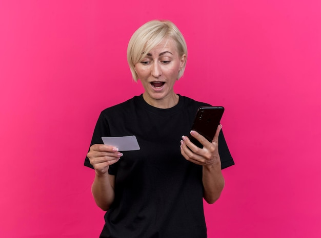 Onder de indruk van middelbare leeftijd blonde slavische vrouw die mobiele telefoon en creditcard houdt die kaart bekijkt die op roze muur met exemplaarruimte wordt geïsoleerd