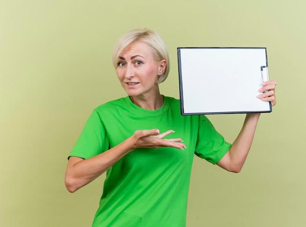 Onder de indruk van middelbare leeftijd blonde slavische vrouw met klembord dichtbij hoofd wijzend met de hand ernaar kijkend naar voorzijde geïsoleerd op olijfgroene muur