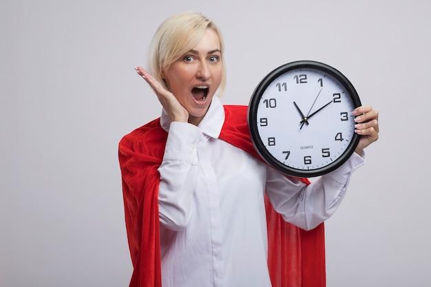 Onder de indruk van middelbare leeftijd blonde superheld vrouw in rode cape met klok hand in de buurt van gezicht houden