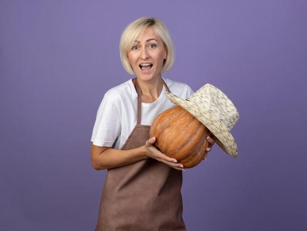 Onder de indruk van middelbare leeftijd blonde tuinman vrouw in uniform met hoed met butternut pompoen met hoed erop