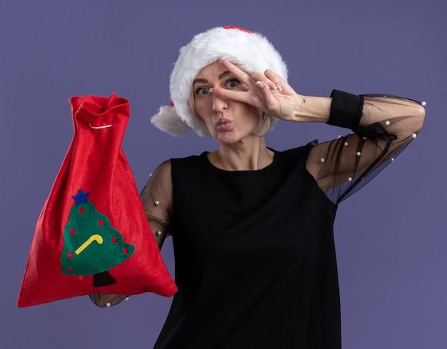 Onder de indruk van middelbare leeftijd blonde vrouw met kerstmuts bedrijf kerstzak kijken camera weergegeven: v-teken symbool in de buurt van oog met samengeknepen lippen geïsoleerd op paarse achtergrond