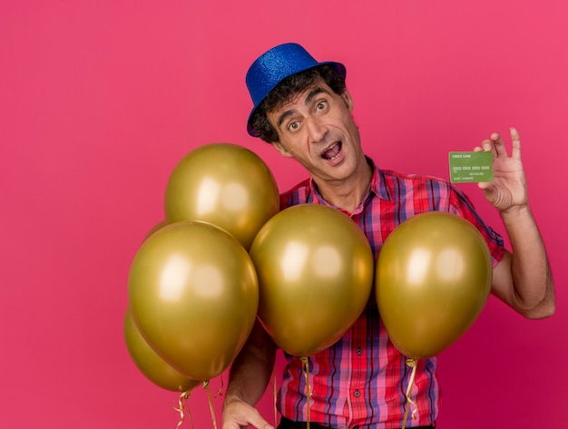 Onder de indruk van middelbare leeftijd feestmens met feestmuts met ballonnen die creditcard tonen die naar voorzijde geïsoleerd op een karmozijnrode muur kijken