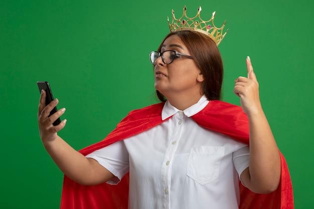 Onder de indruk van middelbare leeftijd superheld vrouwtje dragen kroon met bril houden en kijken naar telefoon punten omhoog geïsoleerd op groene achtergrond