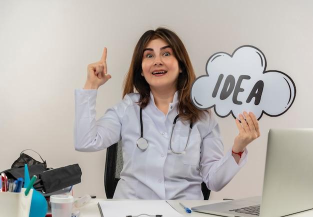 Onder de indruk van middelbare leeftijd vrouwelijke arts die het dragen van medische mantel met stethoscoop zit aan bureau werkt op laptop met medische hulpmiddelen idee zeepbel wijst naar boven op witte muur met kopie ruimte