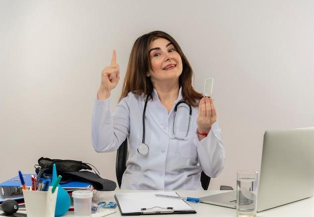 Onder de indruk van middelbare leeftijd vrouwelijke arts die medische mantel en stethoscoop draagt ?? die aan bureau zit met het klembord van medische hulpmiddelen en laptop die gloeilamp houdt en geïsoleerde vinger opheft