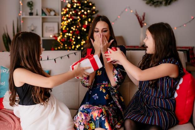 Onder de indruk van twee zussen en jonge opgewonden moeder thuis in de kersttijd zittend op de bank in de woonkamer zusters geven cadeaupakketten aan moeder en ze kijkt naar pakjes terwijl ze de handen op de mond houdt