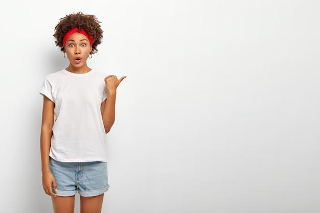 Onder de indruk verbaasde jonge vrouw met een donkere huid wijst naar rechts, toont lege witte kopie ruimte