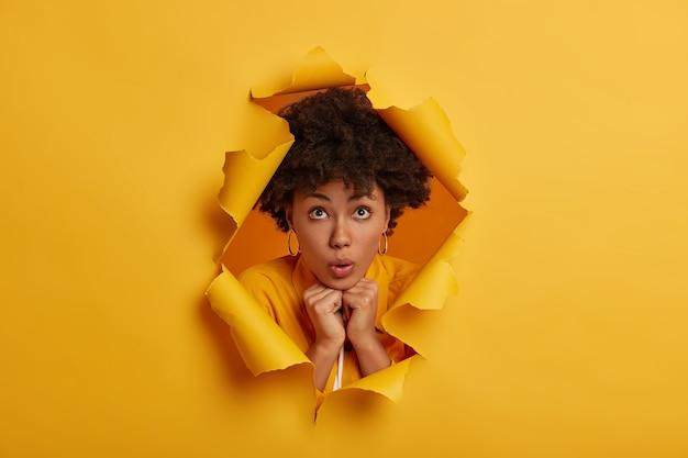 Onder de indruk verrast jonge vrouw, houdt handen samengeperst onder de kin, poses in gescheurd geel papier gat achtergrond