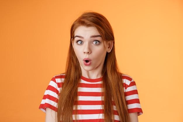 Onder de indruk verrast roodharig meisje trekt verbaasd gezicht, open mond hijgend verbaasd, zeg wow staar camera gefascineerd, sprakeloos hoor geweldige promo, sta oranje achtergrond opgewonden, hoor cool nieuws
